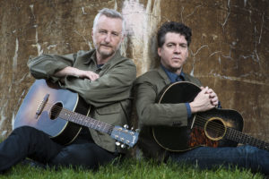 Billy Bragg and Joe Henry sitting on grass with guitars